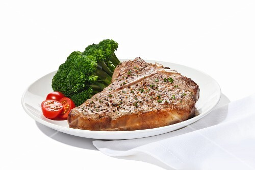 Seasoned T-Bone Steak with Cherry Tomatoes and Broccoli on a White Background