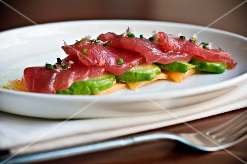 Raw Tuna Slices Over Sliced Avocado on a White Plate