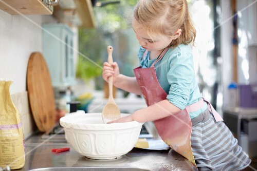 A girl stirring dough in a bowl