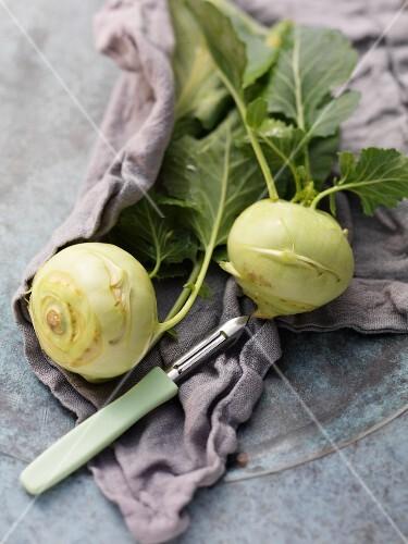 Two kohlrabi with a vegetable peeler