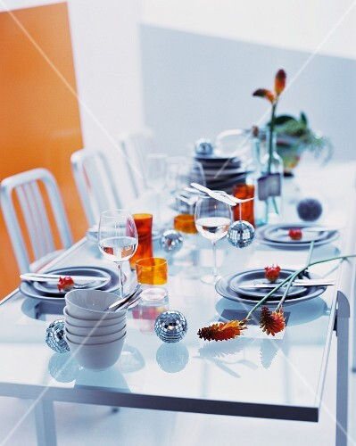 A glass table laid with glasses, bowls, floral decorations and disco balls