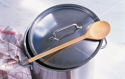 A saucepan with a wooden spoon and a tea towel