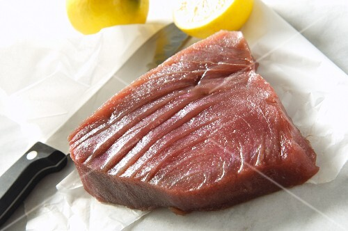 Raw tuna with a knife and lemons