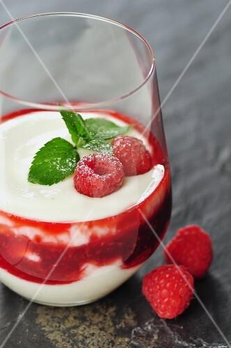 Two glasses with yogurt - quark creme with razberries as dessert, selective focus