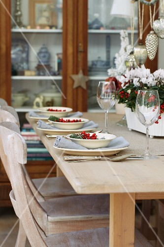A table laid for Christmas next to a glass-fronted cabinet