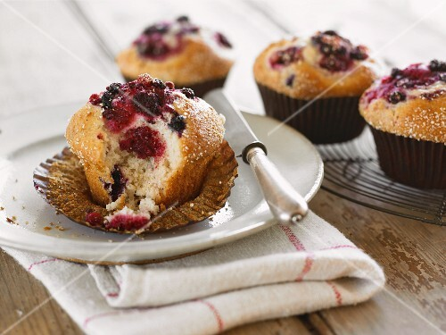 A berry muffin in a paper case, with a bite missing