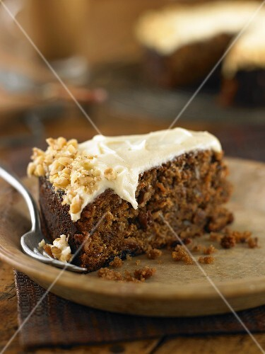 A piece of carrot cake topped with nuts
