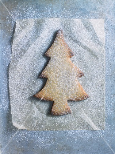 A Christmas tree biscuit dusted with icing sugar, on a piece of grease-proof paper