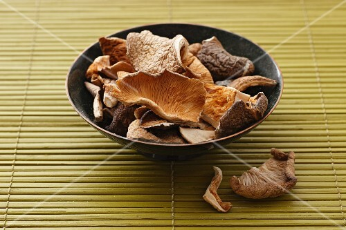 Dried oyster mushrooms in a bowl on a bamboo mat