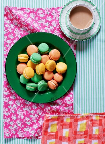 Lots of macaroons on a plate, with a cup of coffee