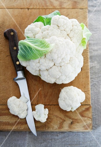 Cauliflower and a knife on a chopping board