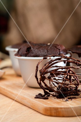 Chocolate melting middle pudding; in the foreground, an egg whisk with remnants of the mixture