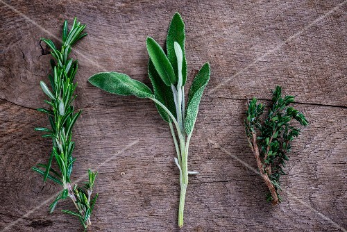Fresh rosemary, sage and thyme on a wooden surface