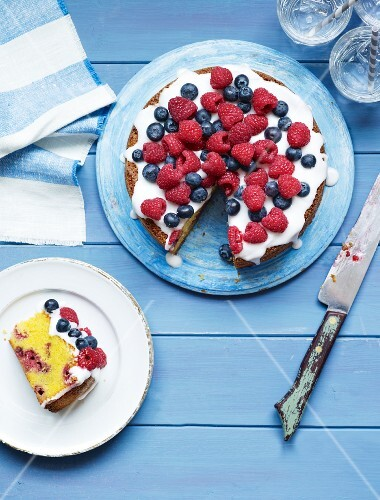 Berry cake with sugar icing, one slice cut