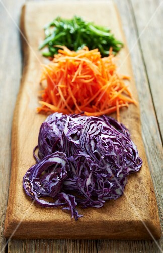 Red cabbage and carrots (grated) on a wooden board