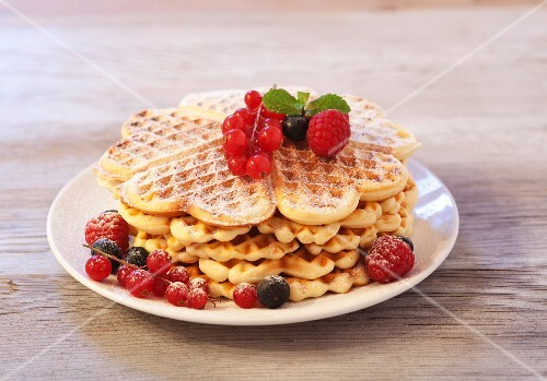 Waffles with raspberries, blueberries and redcurrants on a wooden plate