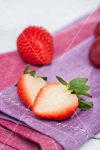 Whole and halved strawberries lying on a napkin