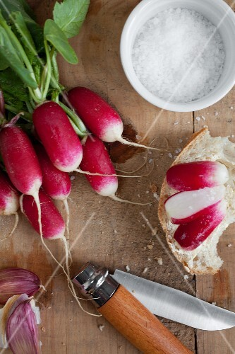 Whole radishes and sliced radishes on bread with salt