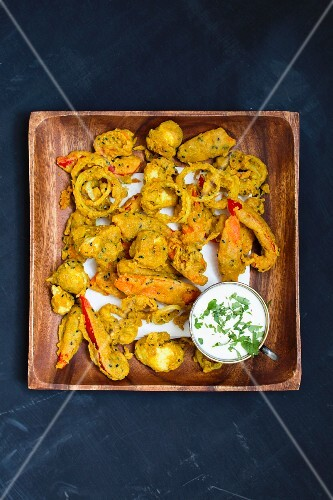Vegetable pakora with raita in a wooden bowl (view from above)