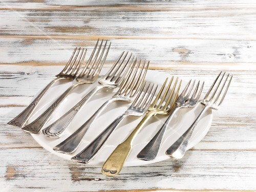 Eight forks in a line lying on a plate