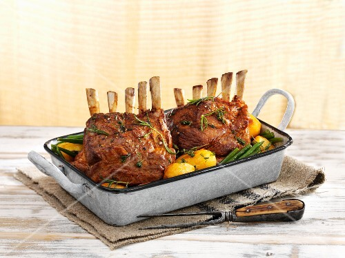 Racks of lamb with potatoes and green beans in a roasting tin