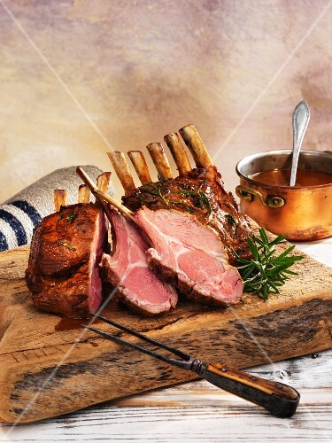 Rack of lamb, cooked pink, on a wooden board