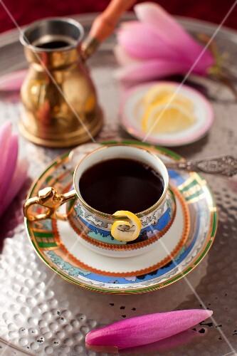A Cup of Coffee with a Lemon Twist and a Pink Flower on a Silver Tray