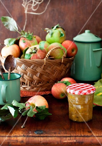 A Jar of Yellow Tomato and Apple Chutney on a Table with a Basket of Fresh Apples