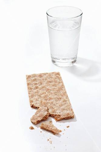 A crispbread and a glass of water