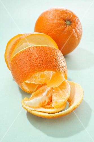 A whole orange, orange peel and orange segments