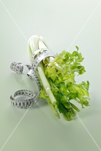 Fresh celery with a measuring tape