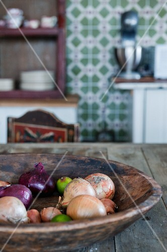 Wooden dish of onions on table; patterned wall tiles in background