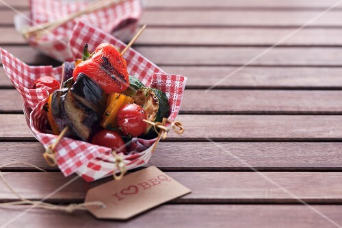 Barbecued vegetables skewers on a napkin in a cardboard container