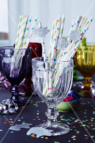 Straws decorated with lucky pigs in glass on a table laid for a party