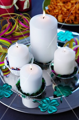 Candles in paper cake cases on silver platter with scattered table confetti
