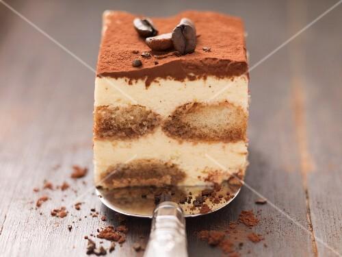 A piece of tiramisu with mocha beans on a cake slice