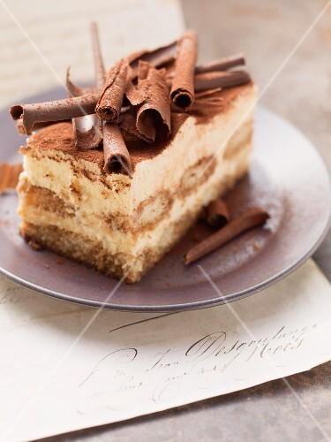 A piece of tiramisu cake topped with rolls of chocolate