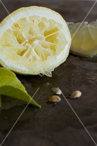 A squeezed lemon half and lemon seeds