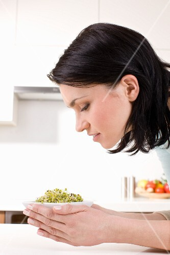 A woman holding a bowl of radish sprouts