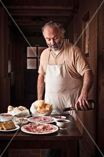 A chef serving red wine with Italian antipasti