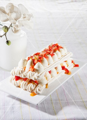 Meringue cake with strawberries and passion fruit sauce