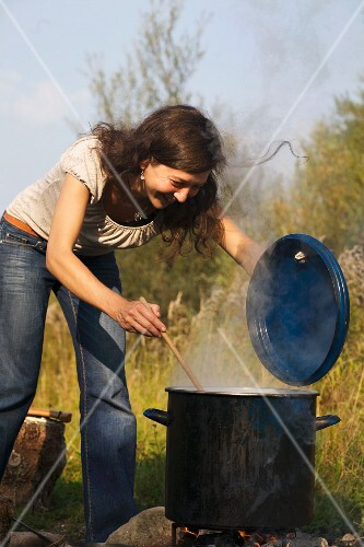 A woman stirring a large pot over an open fire