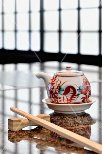 A Japanese table set with chopsticks and a sake pot