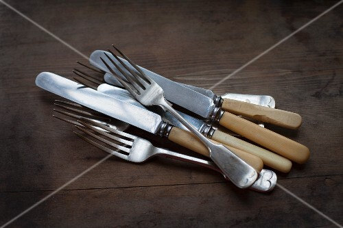 Knives and forks lying on a wooden surface
