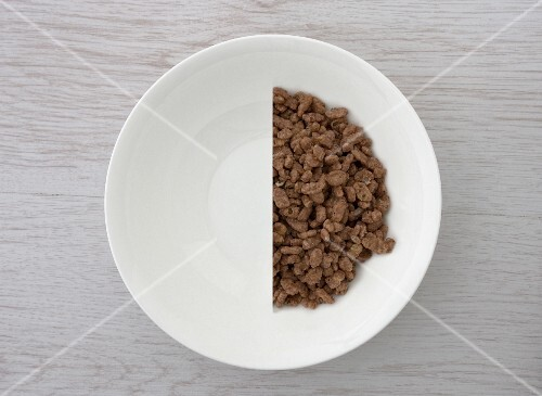 A halved portion of chocolate crisped rice in a white bowl (view from above)