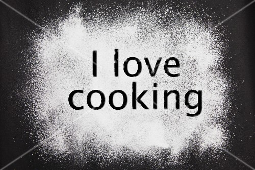 'I love cooking' etched in icing sugar on a black background