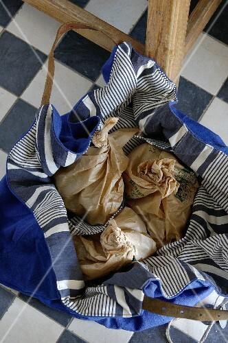 Blue & white striped fabric bag containing paper bags in the kitchen