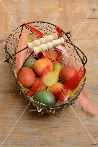 A wire basket of dyed eggs and feathers