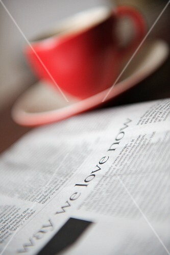 A daily paper next to a cup of coffee