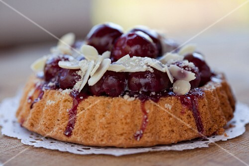 Individual cherry-topped cake with sliced almonds